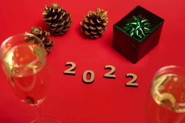 Decoração de natal com algarismos de madeira, ano 2022, presente de natal em papel de embrulho com laço verde brilhante e glitter, pinhas douradas e taças de champanhe com espumante em fundo vermelho