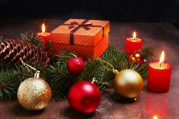 Decoração de natal com caixas de presente, velas vermelhas, árvore de natal e bolas coloridas. foco seletivo.