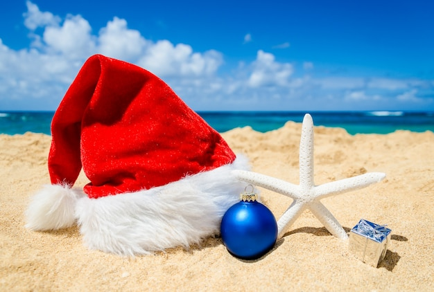 Decoração de natal com chapéu de papai noel e estrela do mar na praia