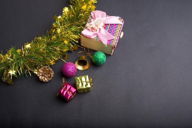 Decoração de natal com fundo preto escuro. vista superior, copie o espaço. bola, caixa de presente, papai noel, fita, pinho de galho, sino.