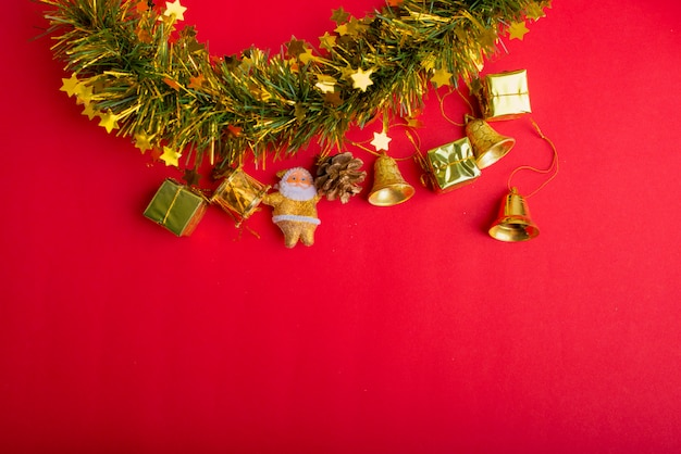 Decoração de natal com fundo vermelho e dourado. vista superior, copie o espaço. caixa de presente, papai noel, ramo de pinheiro, estrelas, sino.