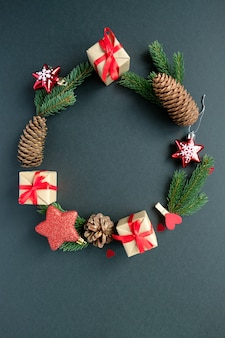 Decoração de natal com galhos, estrelas, caixas de presente e pinha, moldura arredondada em fundo preto