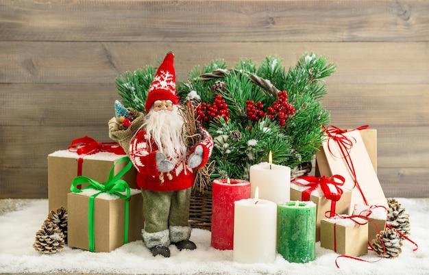 Decoração de natal com o papai noel, velas acesas e caixas de presente. galhos de árvore do abeto na cesta. nenhum brinquedo de nome produzido em massa