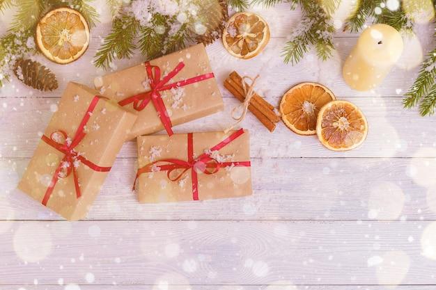 Decoração de natal com presentes, neve, laranja e paus de canela