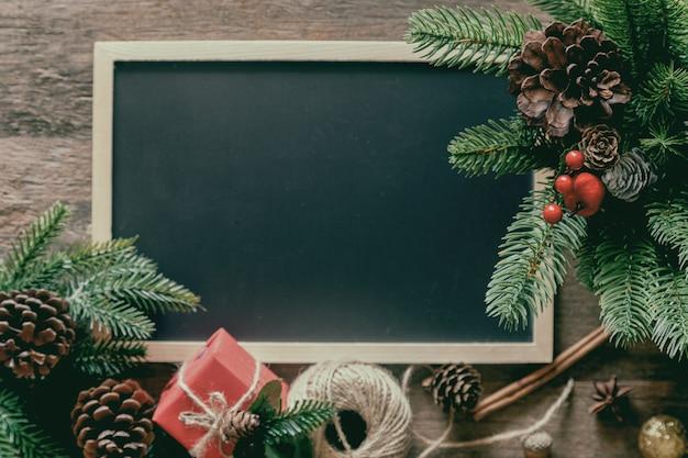 Decoração de natal com quadro-negro, folhas de pinho e cones, caixa de presente e bolas de azevinho