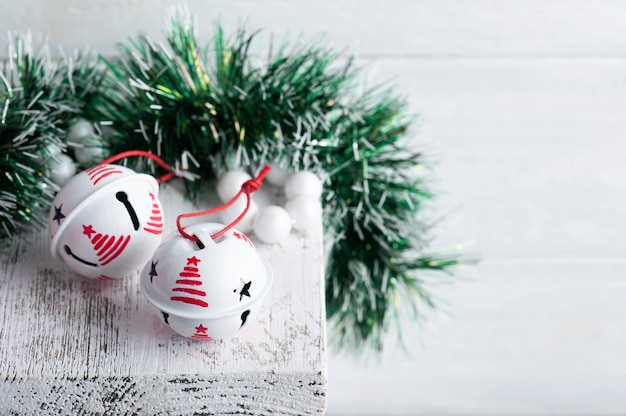 Decoração de natal com sinos brancos sobre fundo branco rústico. copie o espaço para saudações