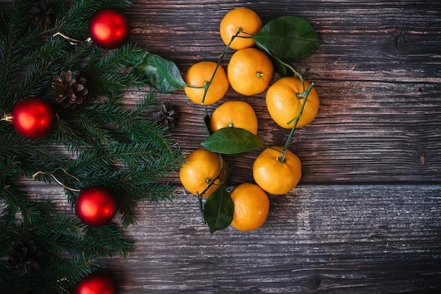 Decoração de natal com tangerinas, ramos de abeto, bolas vermelhas. decoração de inverno festivo tradicional para o ano novo