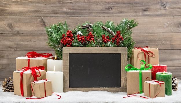 Decoração de natal com velas acesas e caixas de presente. galhos de árvores de natal na cesta. quadro-negro para o seu texto