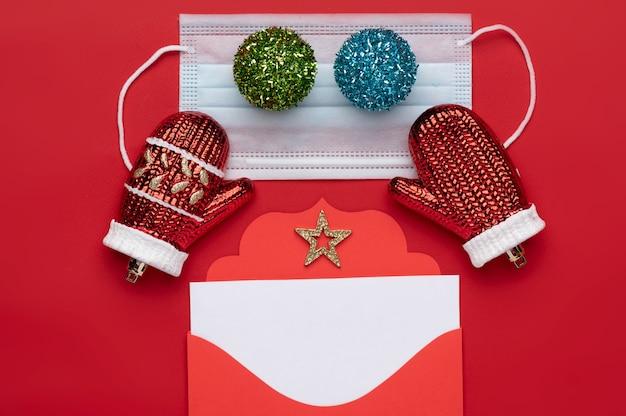 Decoração de natal composta por um envelope de natal vermelho com um timbre branco em branco e duas bolas de natal multicoloridas colocadas em uma máscara médica e o fundo é vermelho