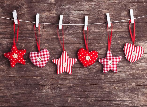 Decoração de natal costurada em vermelho e branco presa à corda, sobre fundo de madeira