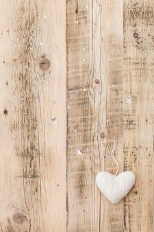 Decoração de natal de coração branco de malha em fundo de madeira retrô com estrelas cintilantes