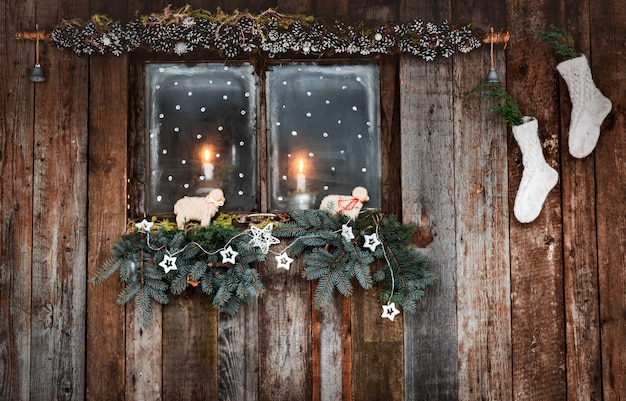 Decoração de natal de paredes de madeira e janelas em estilo rústico. galhos de coníferas e meias brancas à luz de velas pela janela aconchegante.