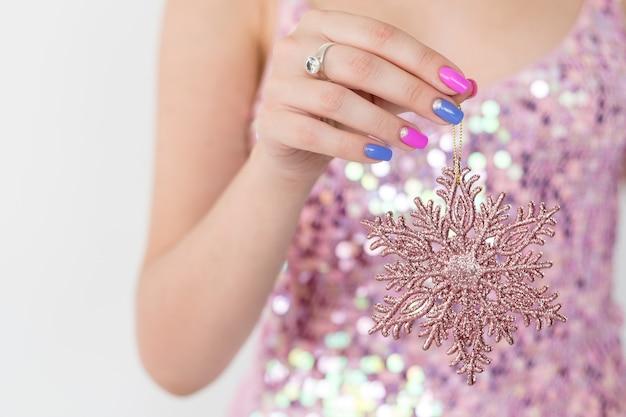 Decoração de natal. decoração do feriado de ano novo e ornamento festivo. mulher segurando um floco de neve brilhante de ouro rosa.