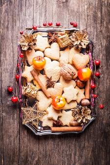Decoração de natal doce - biscoitos, maçã e especiarias na bandeja