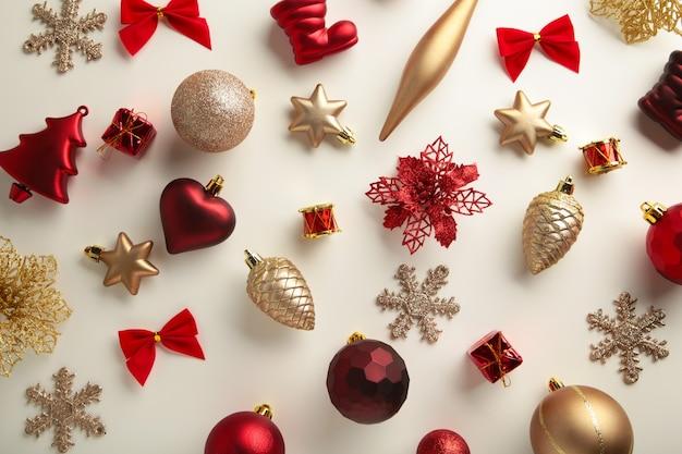 Decoração de natal dourada e vermelha em fundo branco, vista superior, plana leiga. composição de ano novo