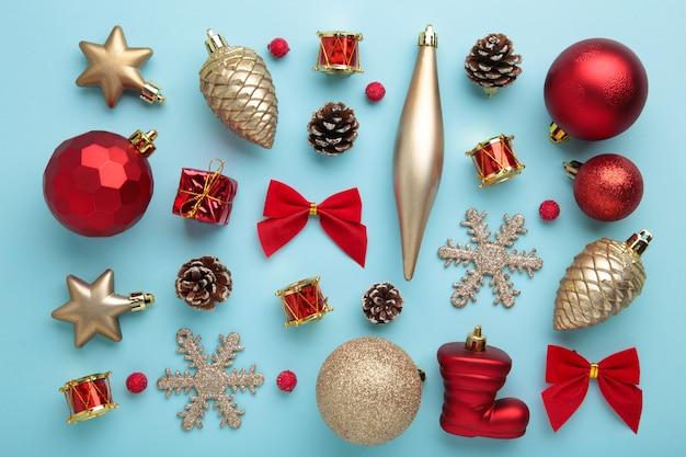 Decoração de natal dourada e vermelha sobre fundo azul, vista superior, plana leiga. composição de ano novo
