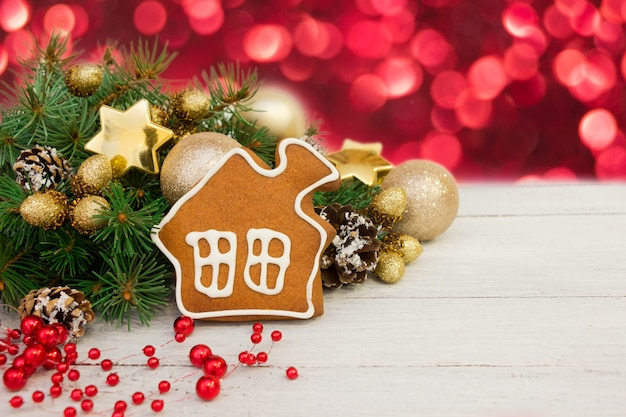 Decoração de natal dourada, pão de mel em forma de casa, galhos de árvores em fundo branco de madeira, bokeh vermelho. cartão postal, espaço para texto