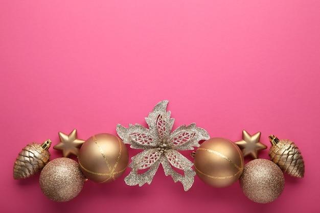 Decoração de natal dourada sobre fundo rosa, vista superior, plana leiga. composição de ano novo