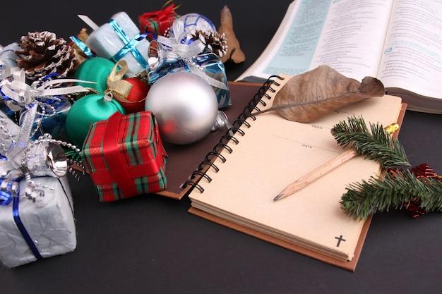 Decoração de natal e a bíblia com pano de fundo preto.