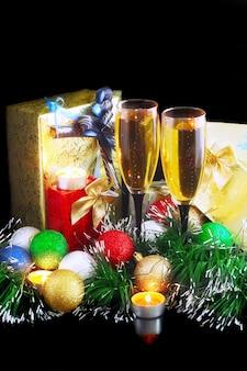 Decoração de natal e ano novo - bolas, enfeites, velas e taças de champanhe. sobre fundo preto.
