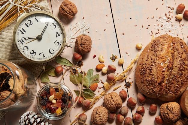 Decoração de natal em estilo rústico e fundo de férias, natureza morta em pano de fundo de madeira, pão, nozes e outros