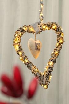 Decoração de natal em forma de coração feito de ramos e luzes