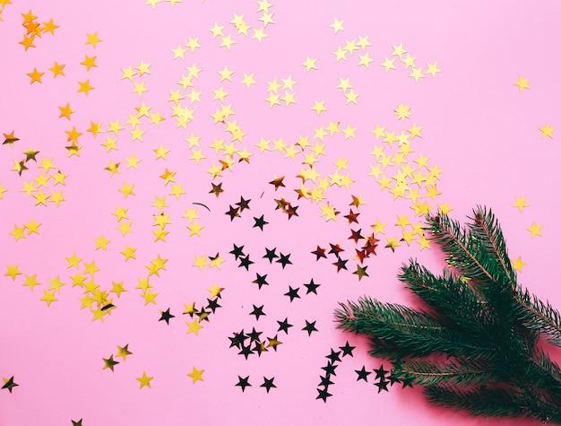 Decoração de natal em um fundo rosa com estrelas douradas