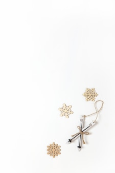 Decoração de natal, esqui de madeira de brinquedo e alguns pequenos flocos de neve no fundo branco, copie o espaço. conceito festivo, ano novo. postura vertical plana. estilo mínimo. vista do topo