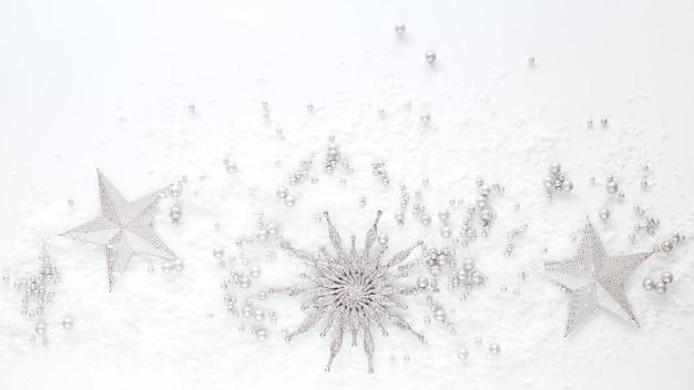 Decoração de natal - estrelas de prata e floco de neve em fundo branco