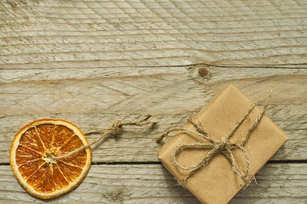 Decoração de natal. fatia de laranja seca e caixa de presente em papel ofício, vista superior, configuração mínima plana