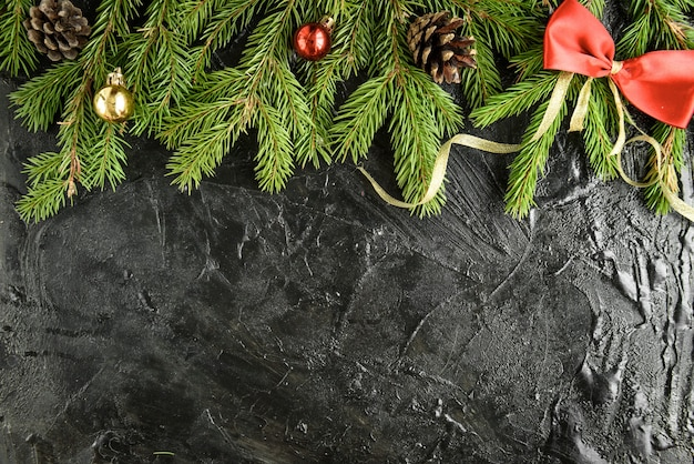 Decoração de natal. galho de árvore do abeto com bolas, presentes, pinha e arcos em uma superfície de madeira preta