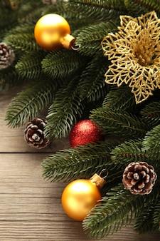 Decoração de natal. galho de árvore do abeto com bolas vermelhas e douradas em fundo cinza