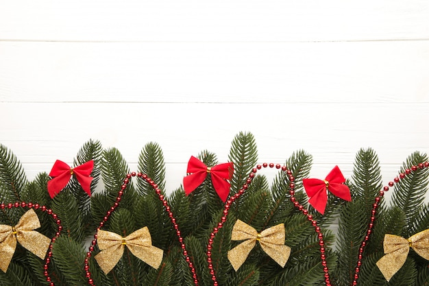 Decoração de natal. galho de árvore do abeto com taças de ouro e vermelhas, miçangas em branco