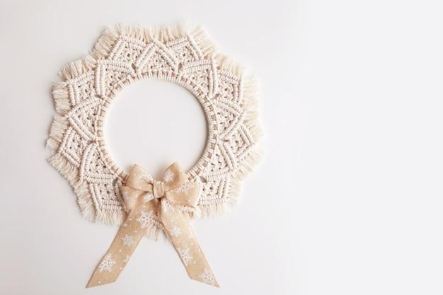 Decoração de natal. guirlanda de macrame em uma parede de gesso decorativo branco. fio de algodão natural, fita de linho. eco decoração para casa