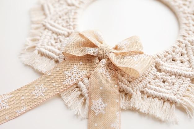 Decoração de natal. guirlanda de macramé para o natal e o ano novo em uma parede de gesso decorativo branco. fio de algodão natural, fita de linho. eco decoração para casa