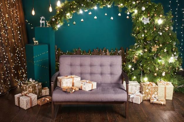 Decoração de natal. interior bem iluminado com uma grande árvore de natal, um sofá aconchegante cinza e grandes guirlandas brilhantes nas paredes. férias de inverno