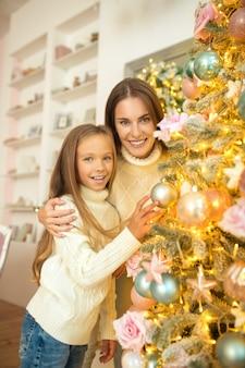 Decoração de natal. mãe e filha decorando árvore de natal juntas e se sentindo bem