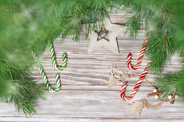 Decoração de natal nos galhos da árvore de natal. bastões de doces e brinquedos de madeira com fundo de madeira com luz e bokeh.