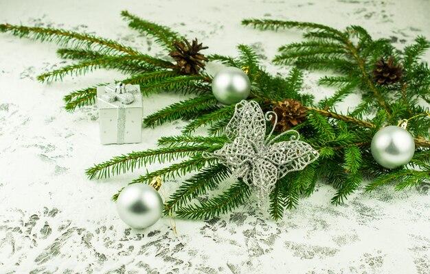 Decoração de natal para o feriado. um ramo de abeto verde com bolas de prata e uma borboleta cintilante em um fundo coberto de neve. ângulo próximo.
