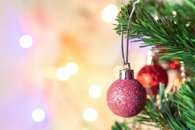 Decoração de natal. pendurar as bolas de glitter rosa em galhos de pinheiro, guirlanda de árvore de natal e ornamentos sobre fundo abstrato bokeh com copyspace