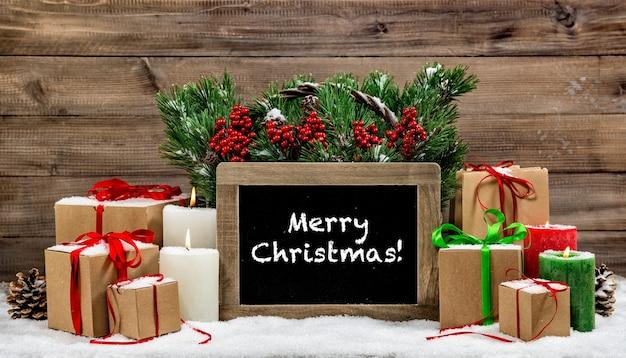 Decoração de natal queimando velas e caixas de presente. quadro-negro com texto de exemplo feliz natal! foto tonificada estilo vintage