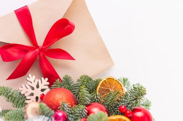 Decoração de natal, ramos de pinheiro, envelope com uma fita vermelha