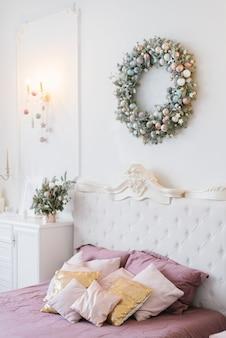 Decoração de natal rosa e branco no quarto clássico, travesseiros na cama e uma coroa de flores sobre a cama