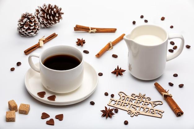 Decoração de natal. xícara de café expresso com leite, cone de árvores de natal e texto de madeira feliz natal
