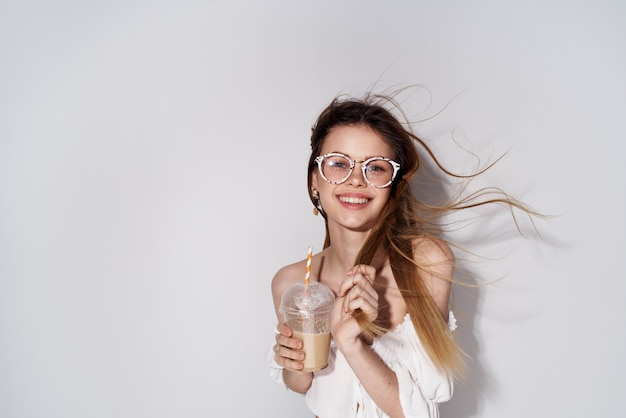 Decoração de óculos na moda de mulher bonita sorriso de vidro com fundo claro de bebida charme. foto de alta qualidade