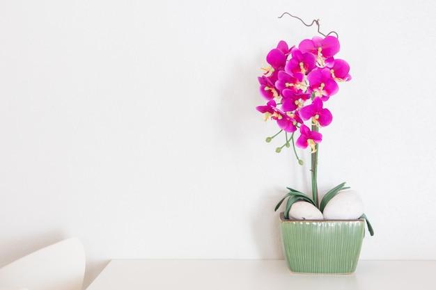 Decoração de orquídeas violeta na mesa de jantar branca