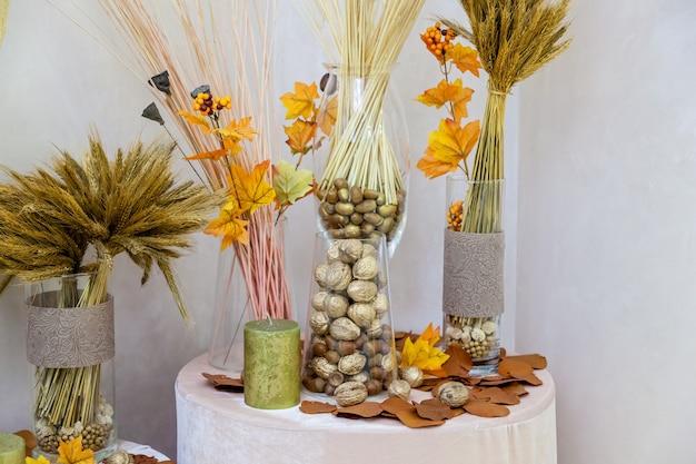 Decoração de outono de nozes de folhas amarelas e velas. decoração de outono para interior artesanal