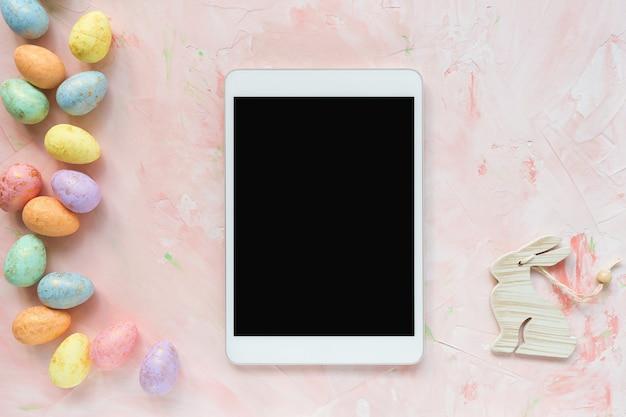 Decoração de ovos coloridos e tablet em um rosa. páscoa .