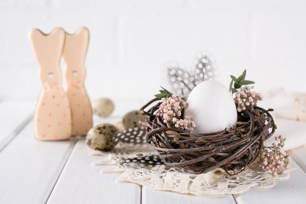 Decoração de ovos de páscoa ninho com ovo de galinha branca. feliz páscoa ou primavera cartão
