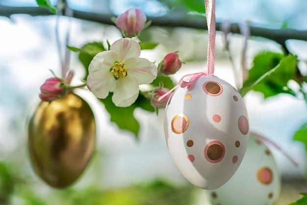 Decoração de ovos em galhos de macieira florida em uma árvore em um jardim ou parque